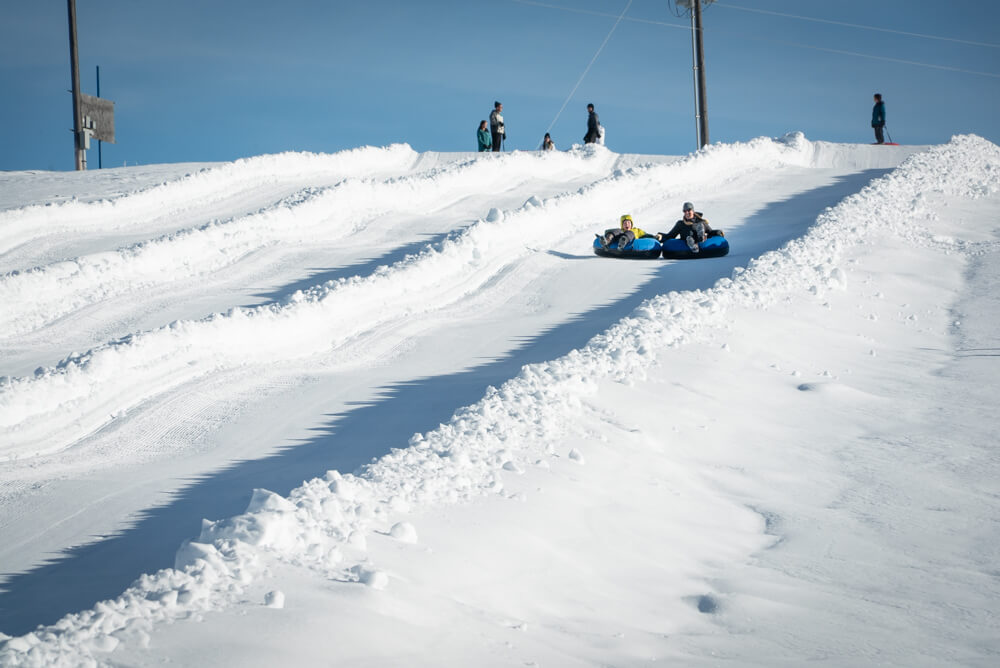 people in tube going down snowy tubing hill