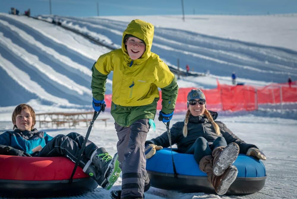 boy pulling people on snowy tubing hill