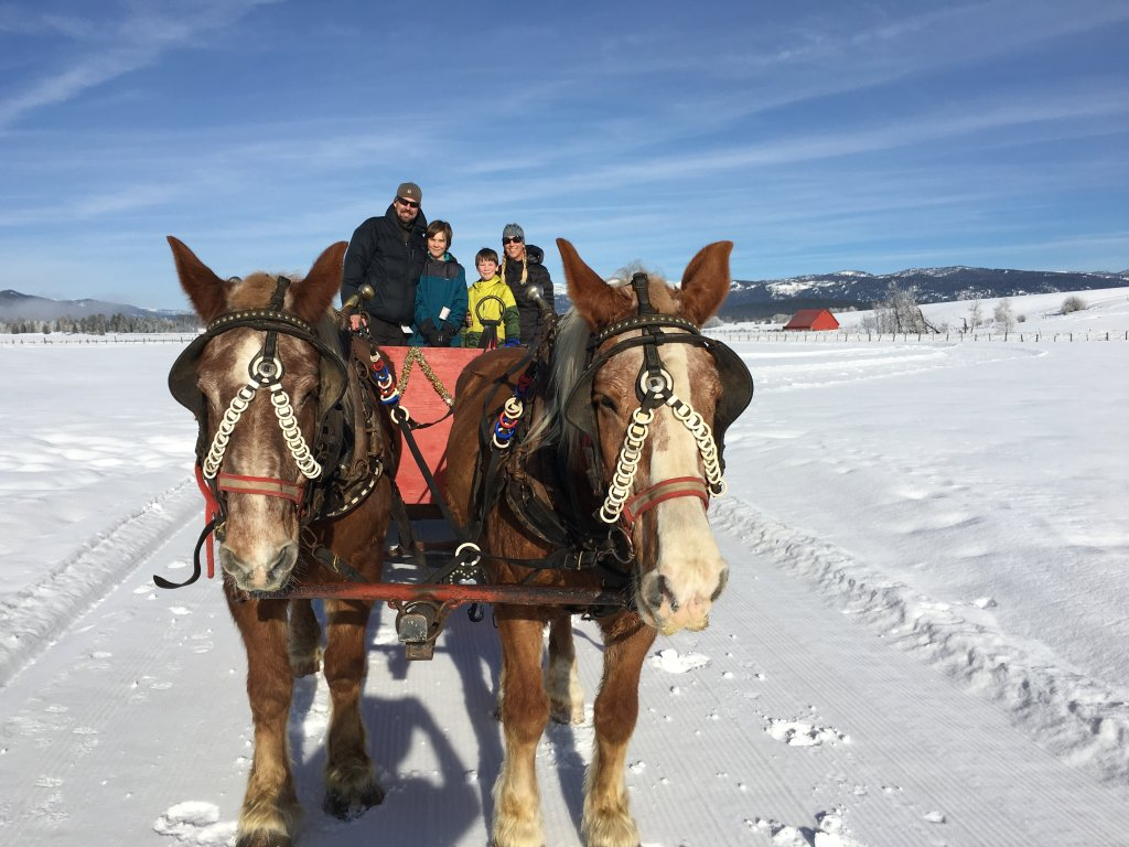 family on horse drawn sleigh at McCall activity barn