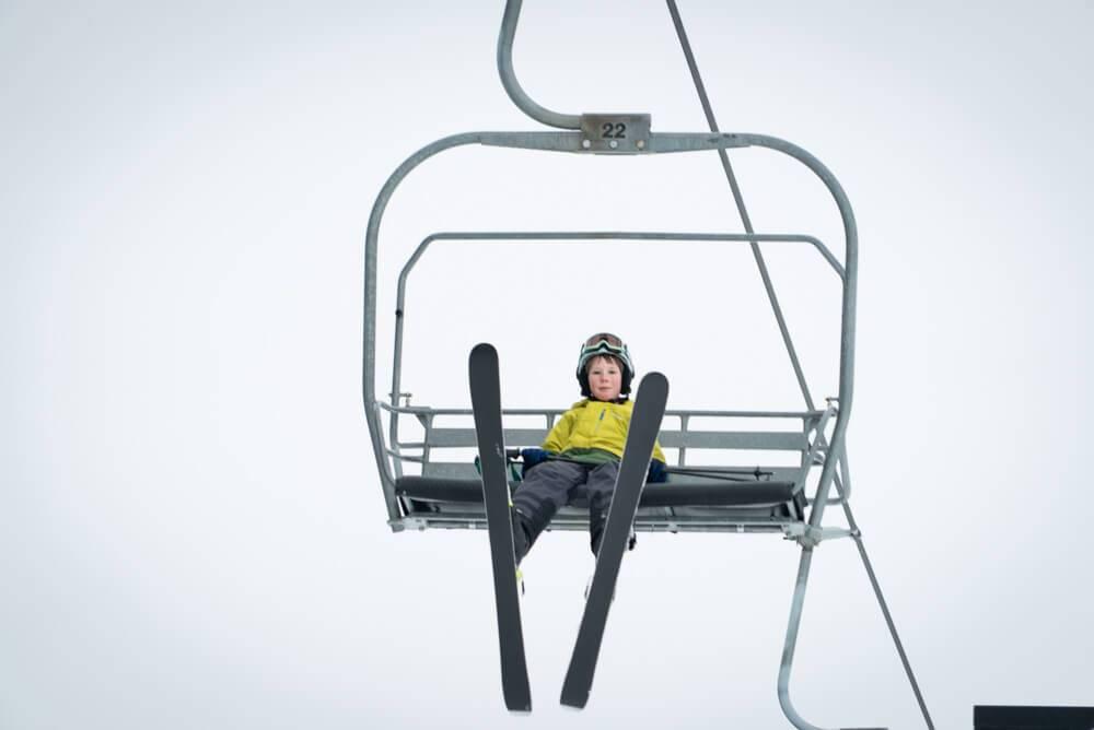 child sitting on ski lift