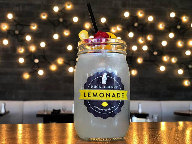 a lemonade cocktail in a jar topped with fruit on a table with booths in the background
