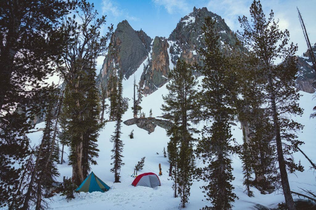 two small tents against snowy mountains
