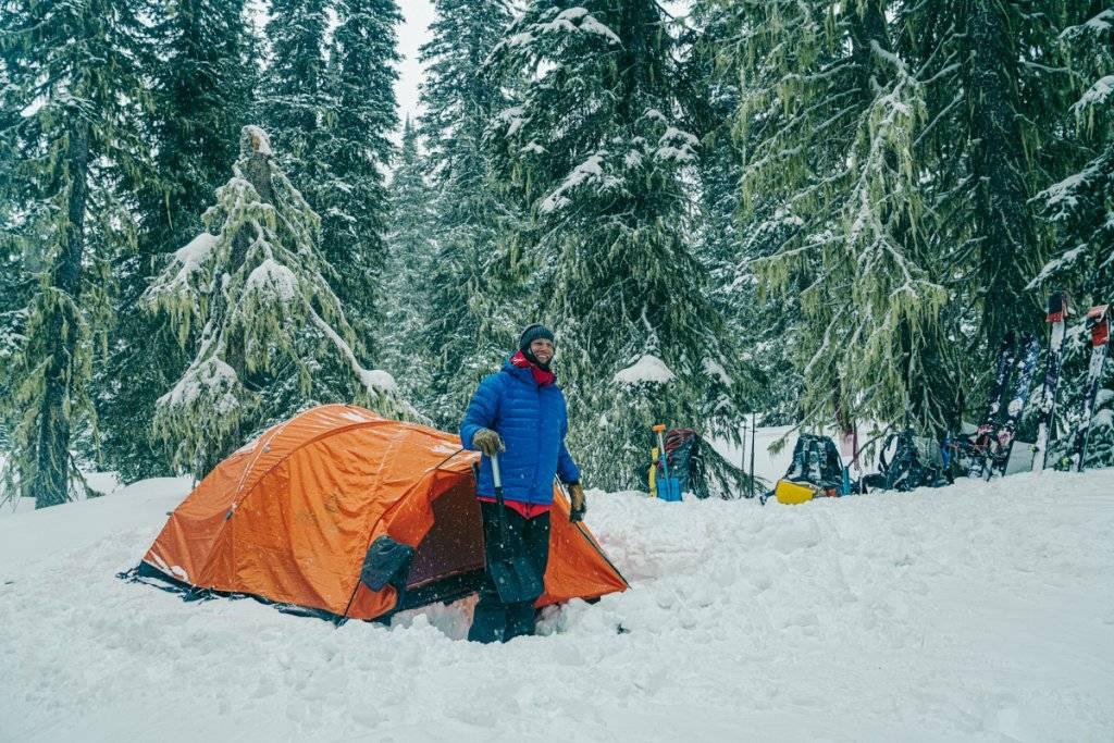 man standing outside snowy ten