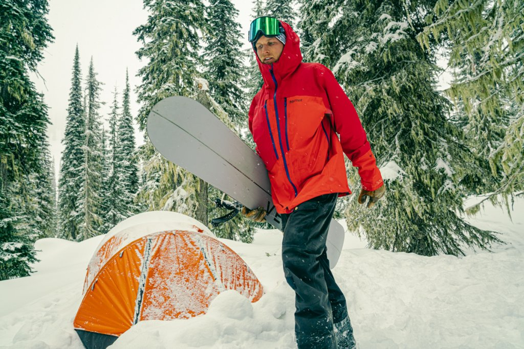 man with splitboard in snow with tent