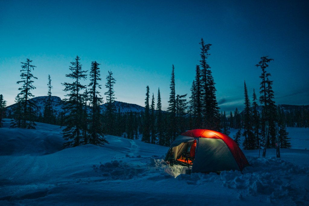 tent with light inside at dusk on the snow