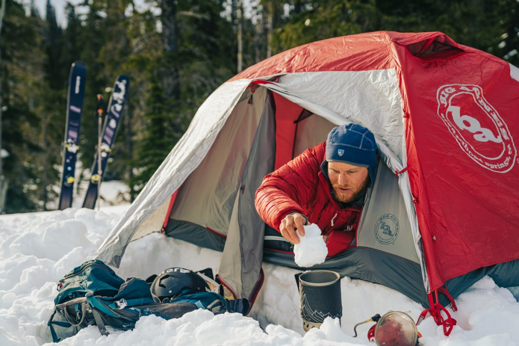 man boiling snow to make water outside tent surrounded by snow