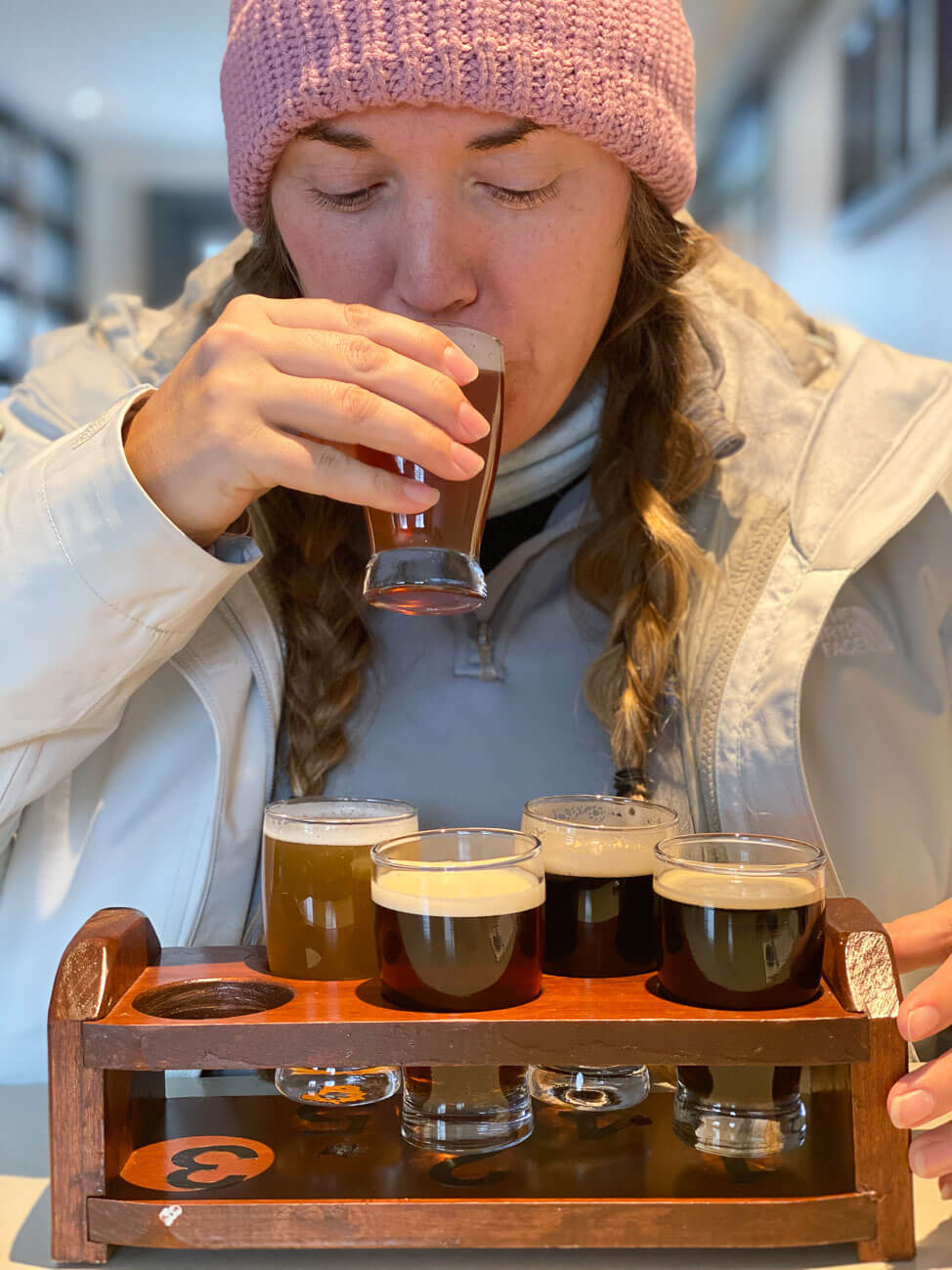 woman drinking flight of beers at Sawtooth Brewery