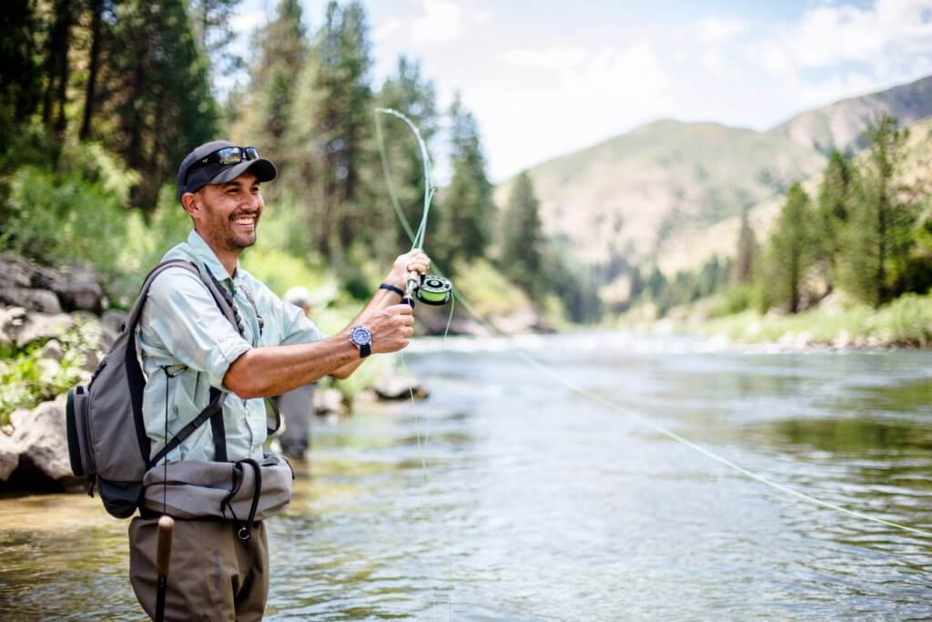 smiling man in a hat casting a fishing line into the river