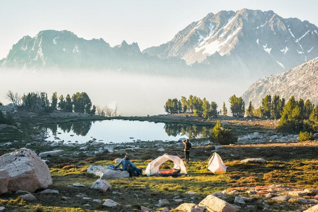 two people at a lakeside campsite with mountains in the distance
