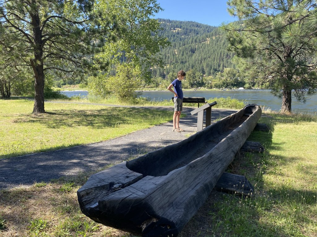 child standing next to historical canoe