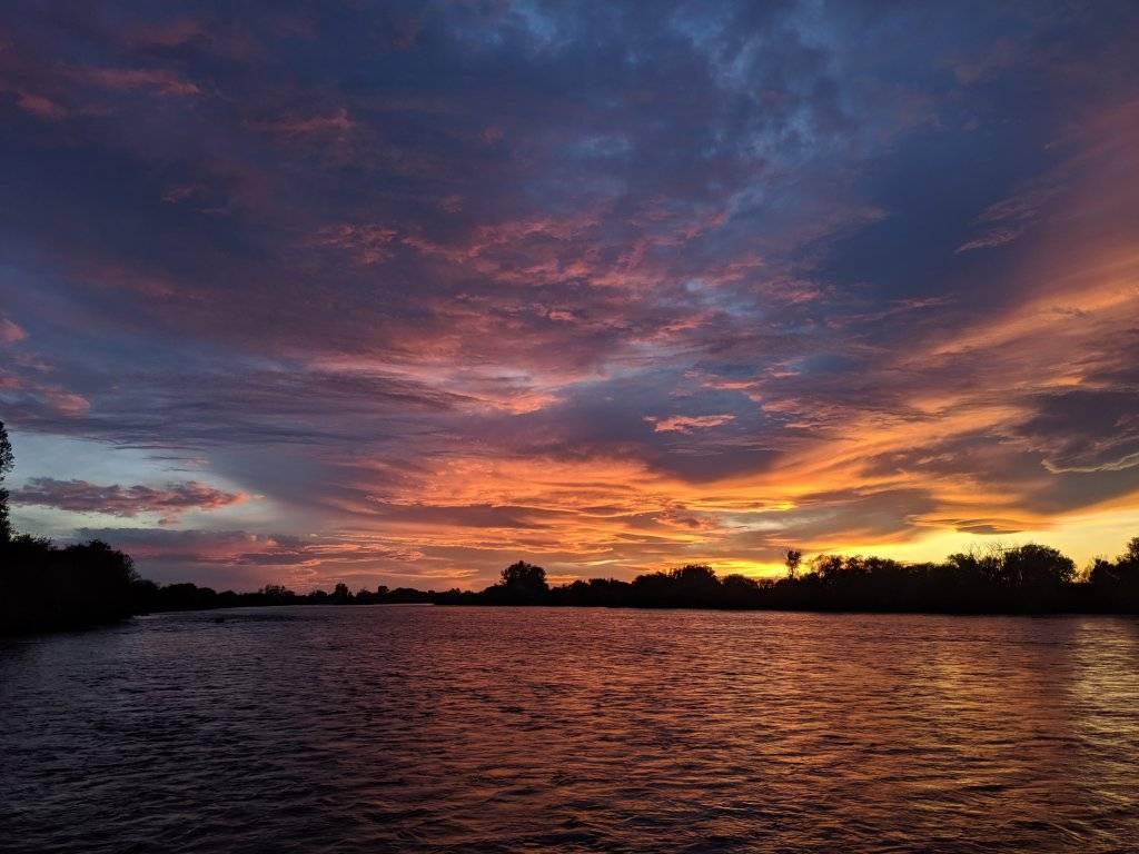 orange, pink and blue sunset over river