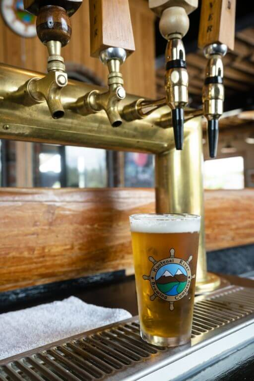 beer in pint glass sitting under beer tap