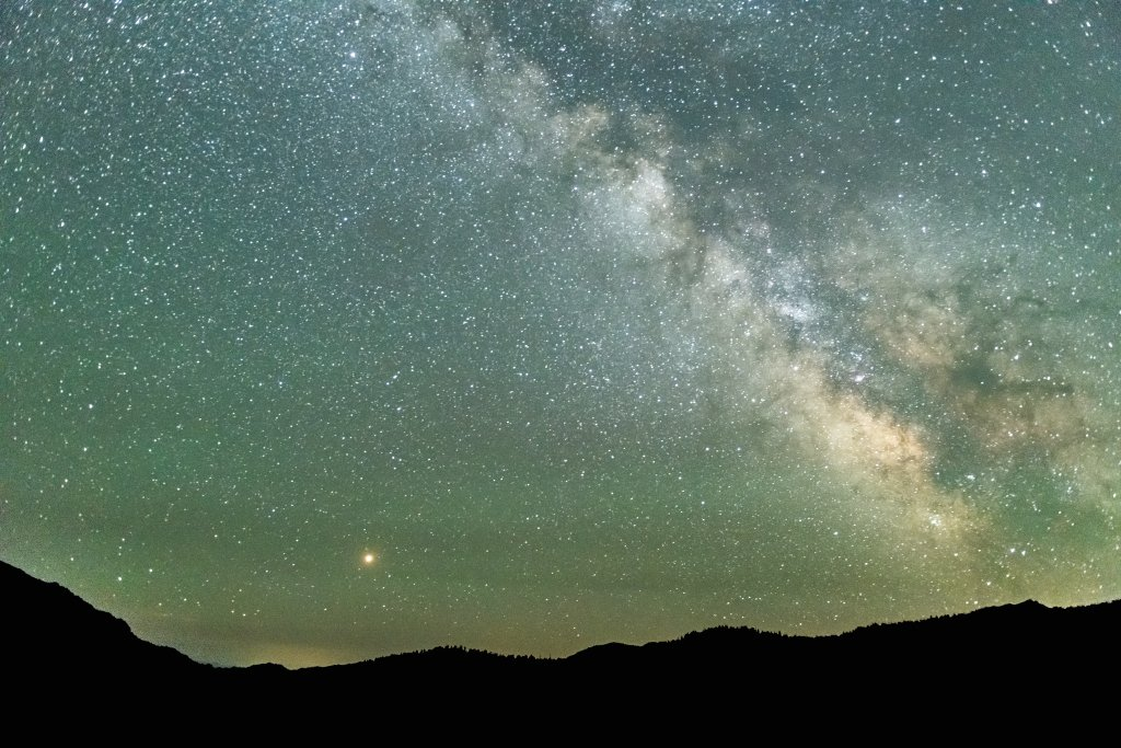 A green starry night sky of the Milky Way and Saturn at the Central Idaho Dark Sky Reserve