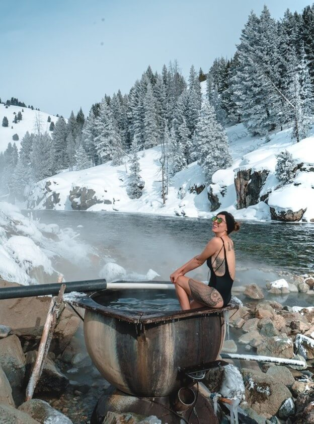 woman sitting along side river in hot spring
