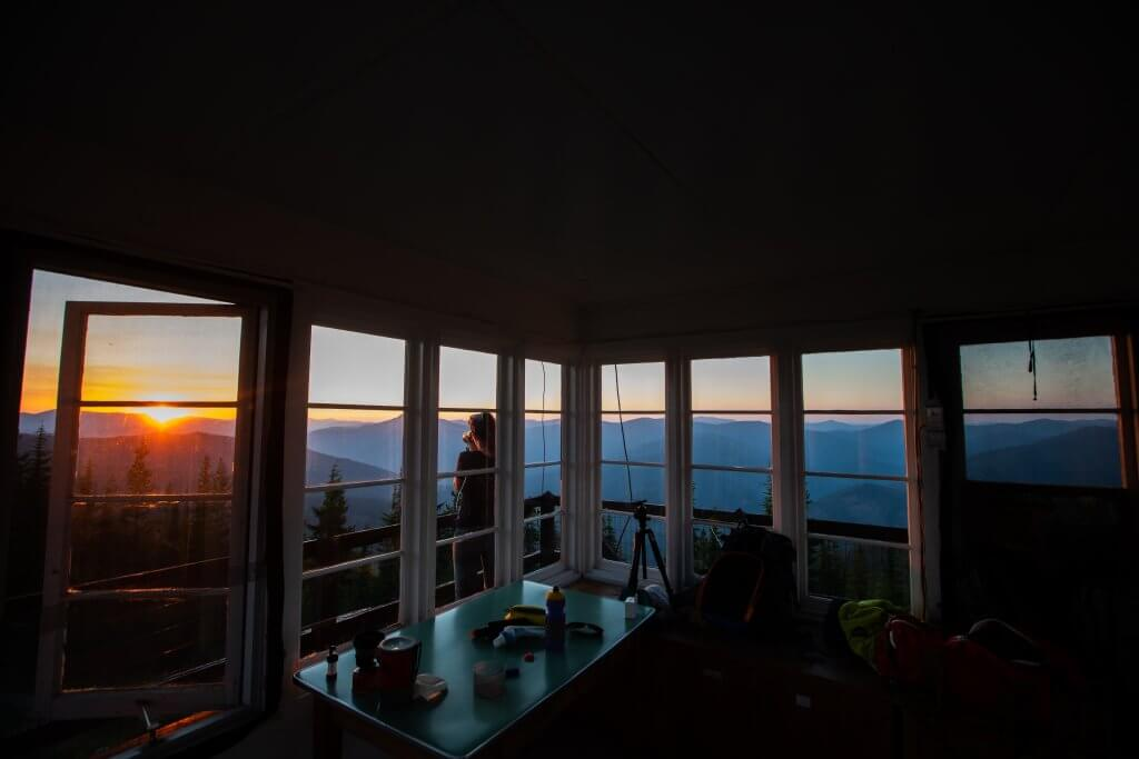 woman standing outside a fire lookout looking at sunset