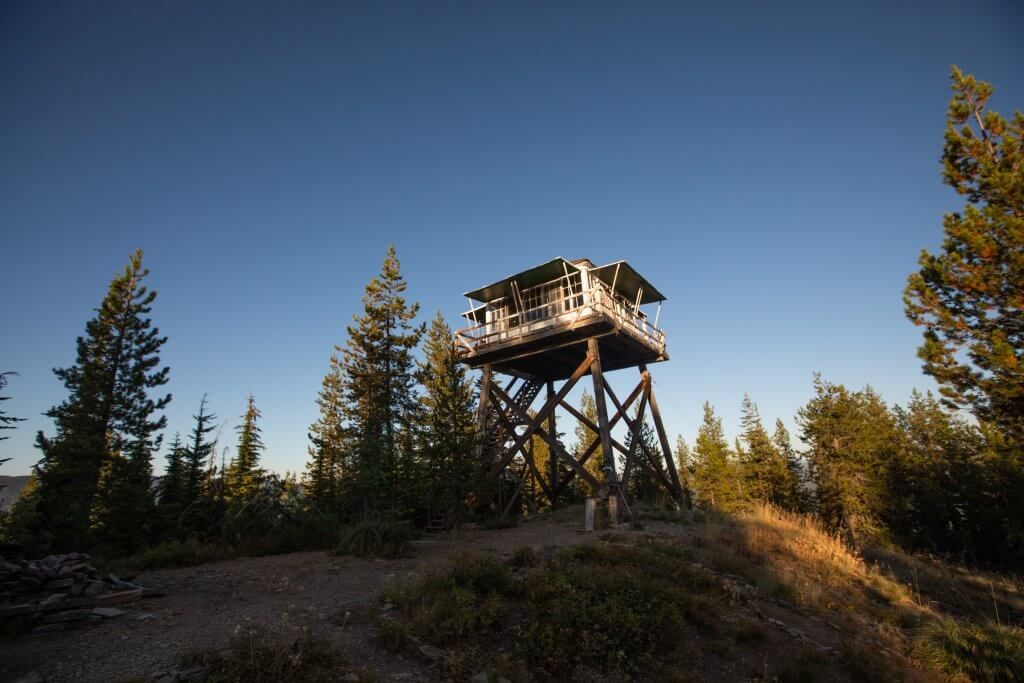 exterior of fire lookout with two women standing at base