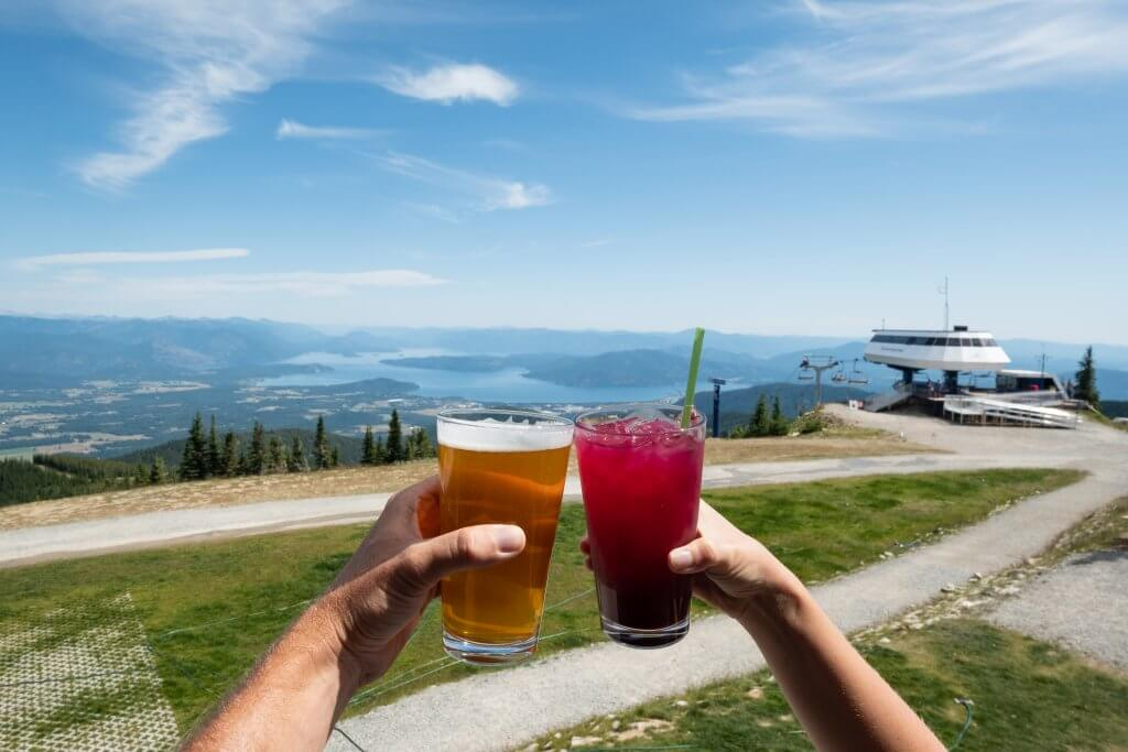 people holding cocktails with a lake in the background