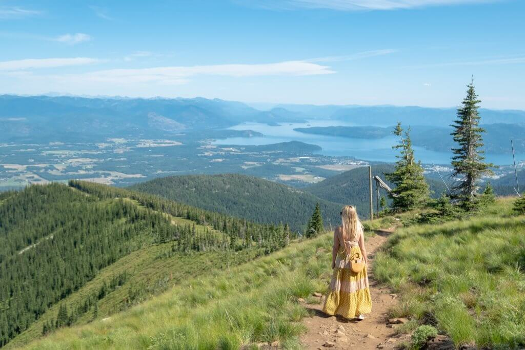 woman high on mountain looking at lake