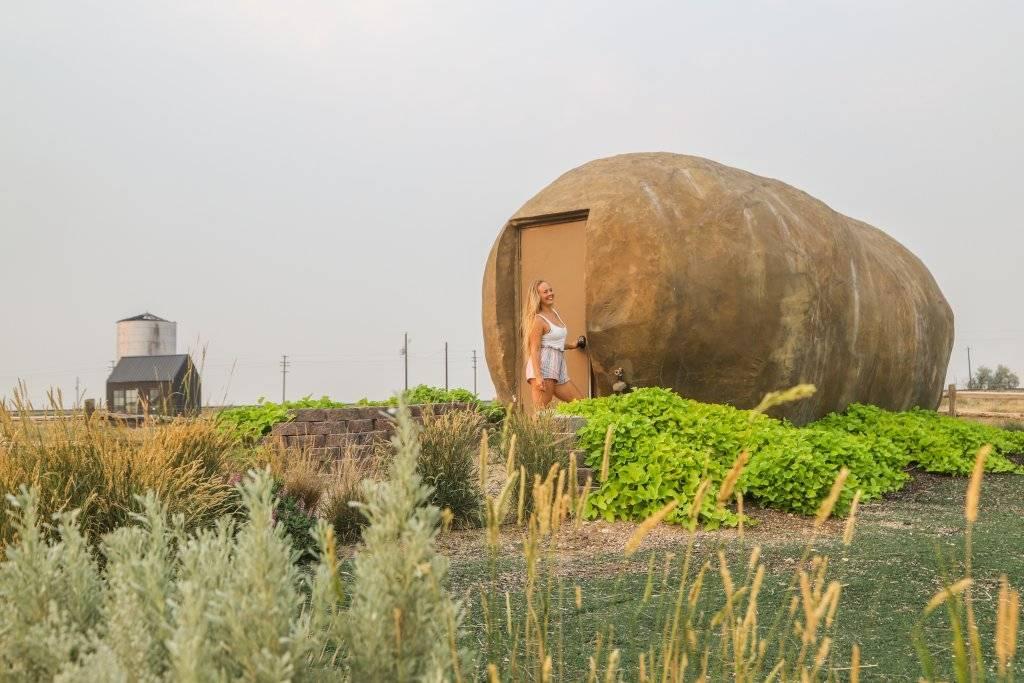 woman standing at door to large idaho potato shaped hotel