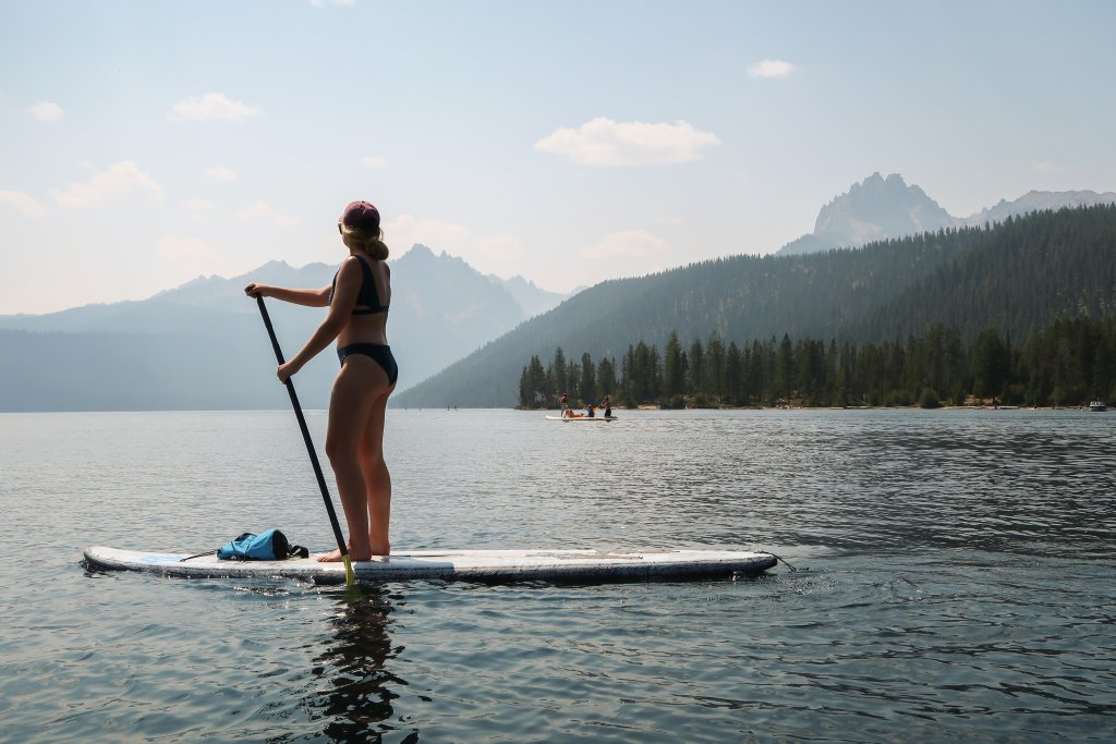 woman on paddle board on lake