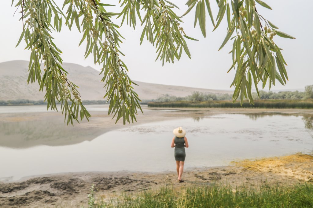 woman standing on edge of small lake