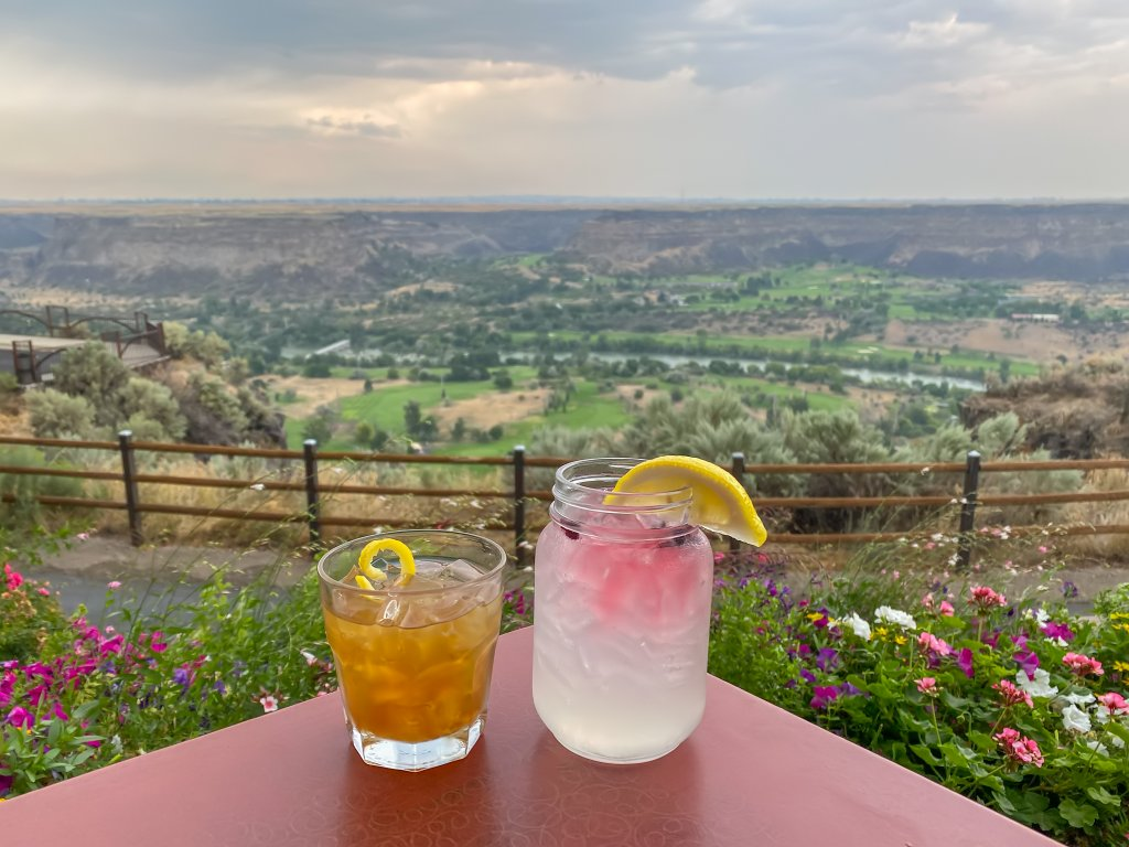 two cocktails on table overlooking snake river canyon