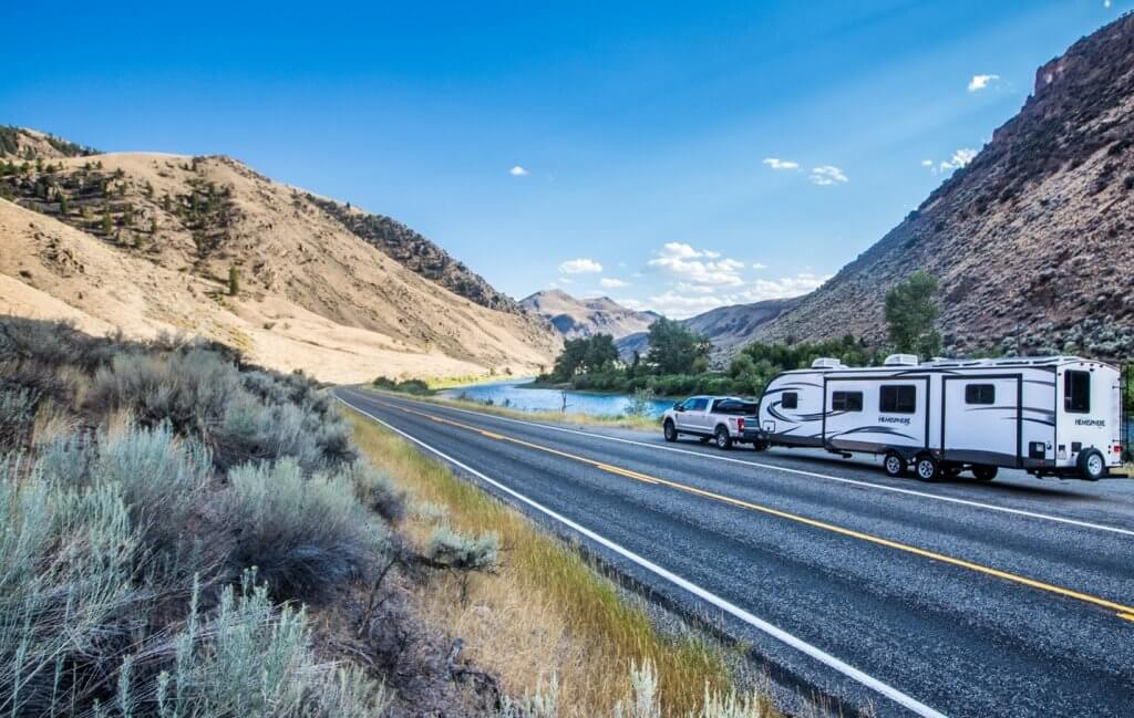 truck pulling large camper on scenic road