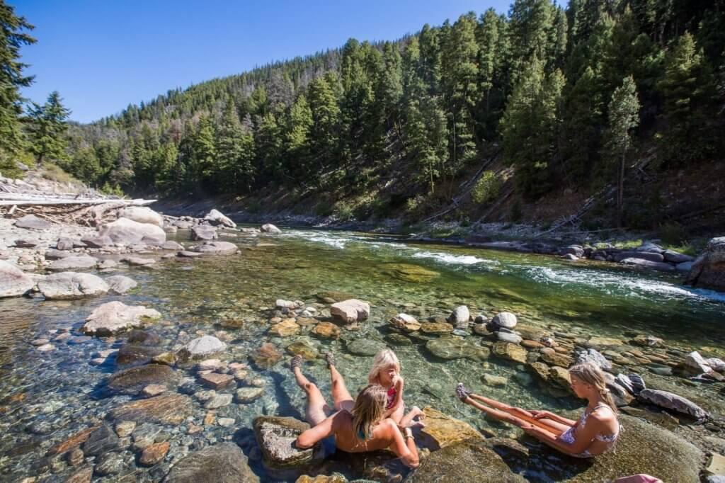 people sitting in riverside hot spring