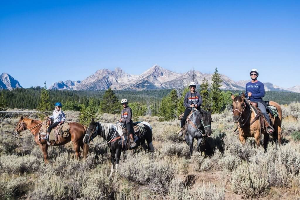 four people on horseback with mountains in background