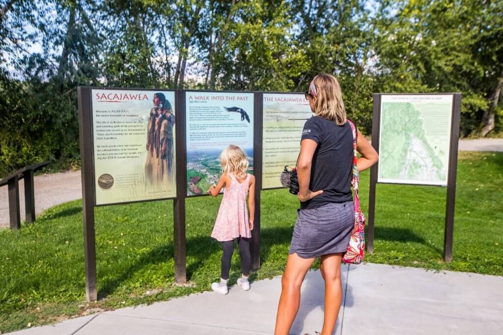 two children and parent reading interpretive signs at sacajawea center