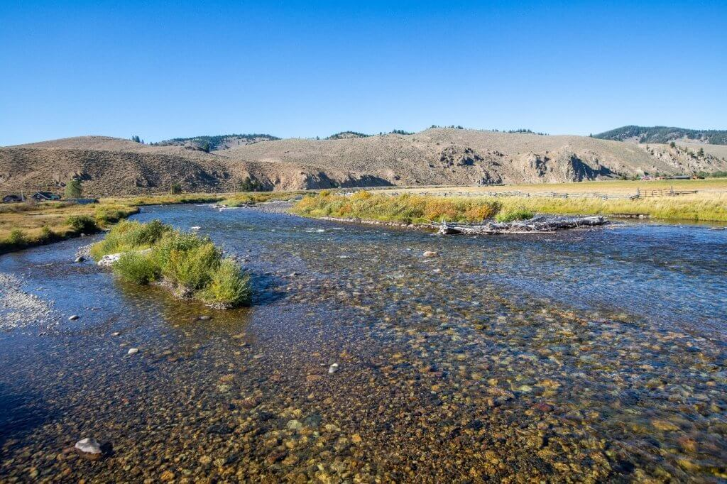 scenic view of salmon river with mountains in background