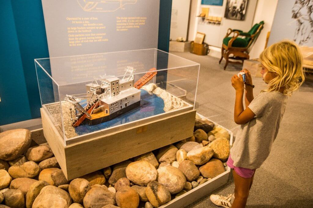 girl look at exhibit of gold dredge