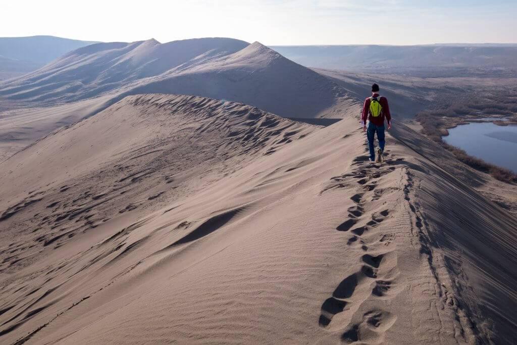 man walking on ridge of sand dune