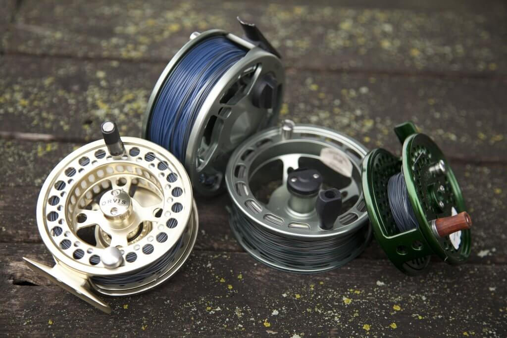 four fly fishing reels grouped together