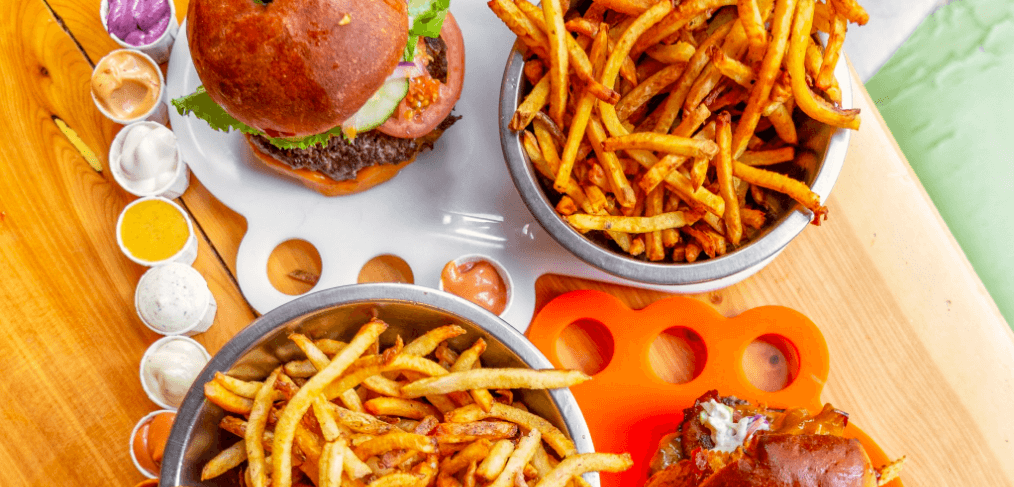 top view of two burgers and two bowls of fries on a wooden table