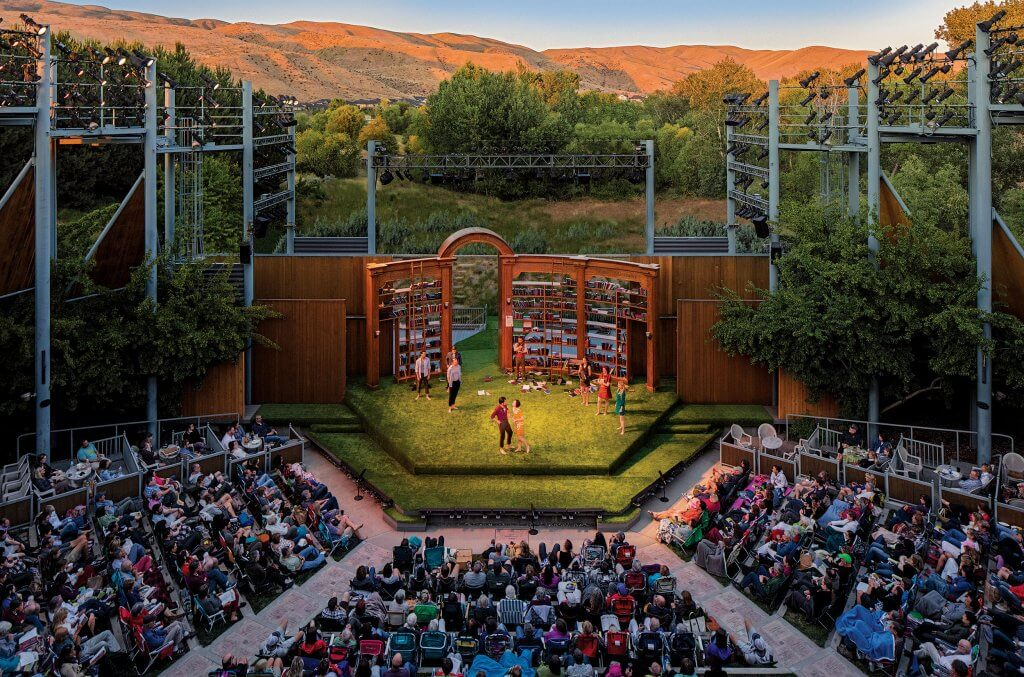 a crowd of people watching a performance at an outdoor amphitheater