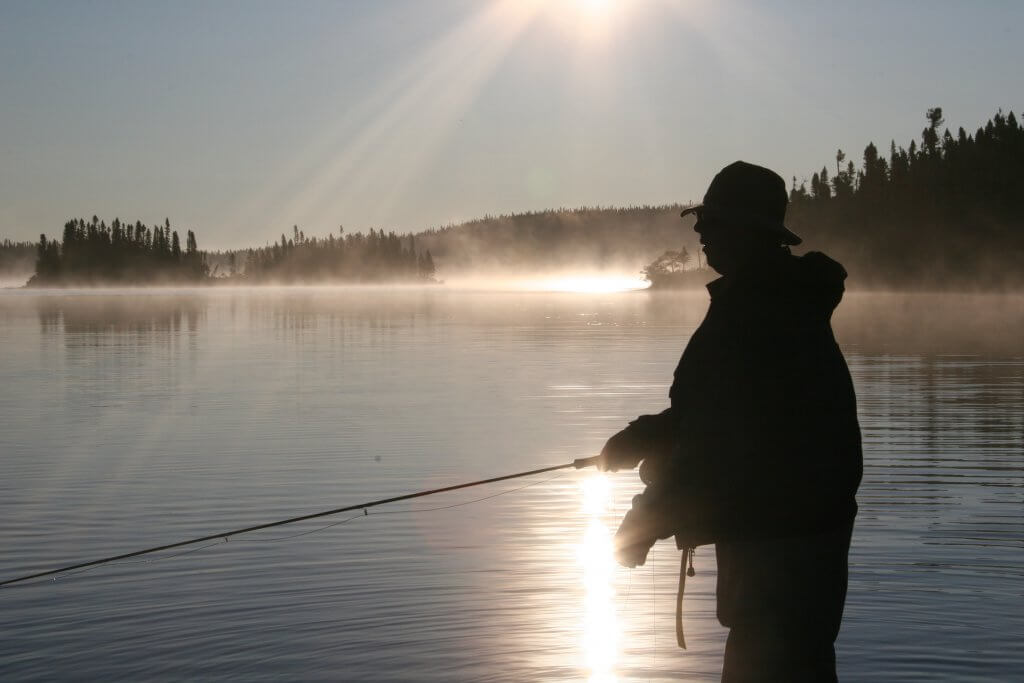 silhouette of man fly fishing in river