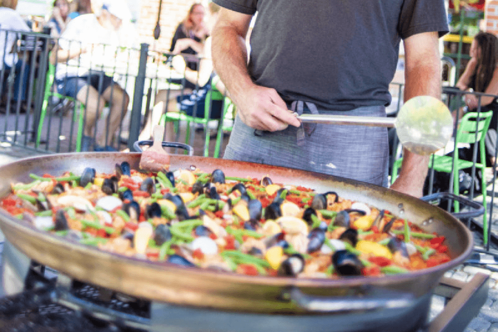 man cooking paella outside and people sitting at tables in the background