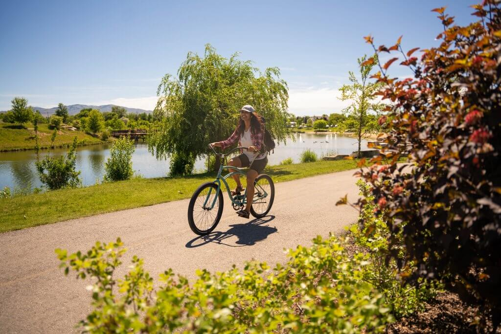 woman on bike on paved path near pond