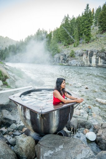 a woman sitting in a hot spring next to a river