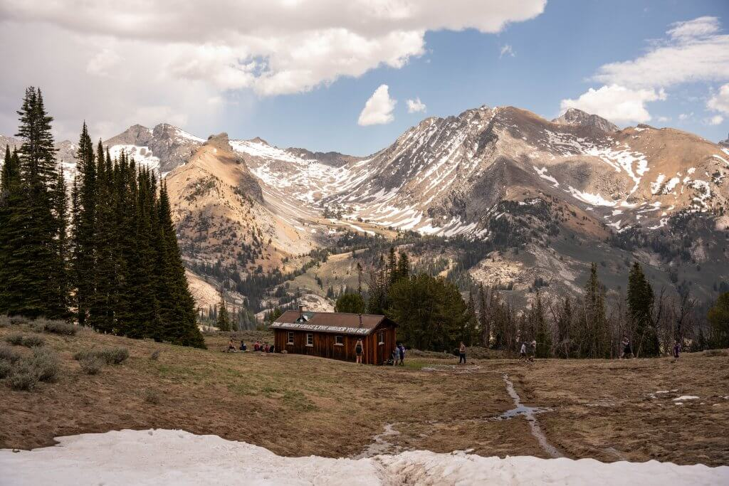 mountain cabin with grand mountains behind it in the distance