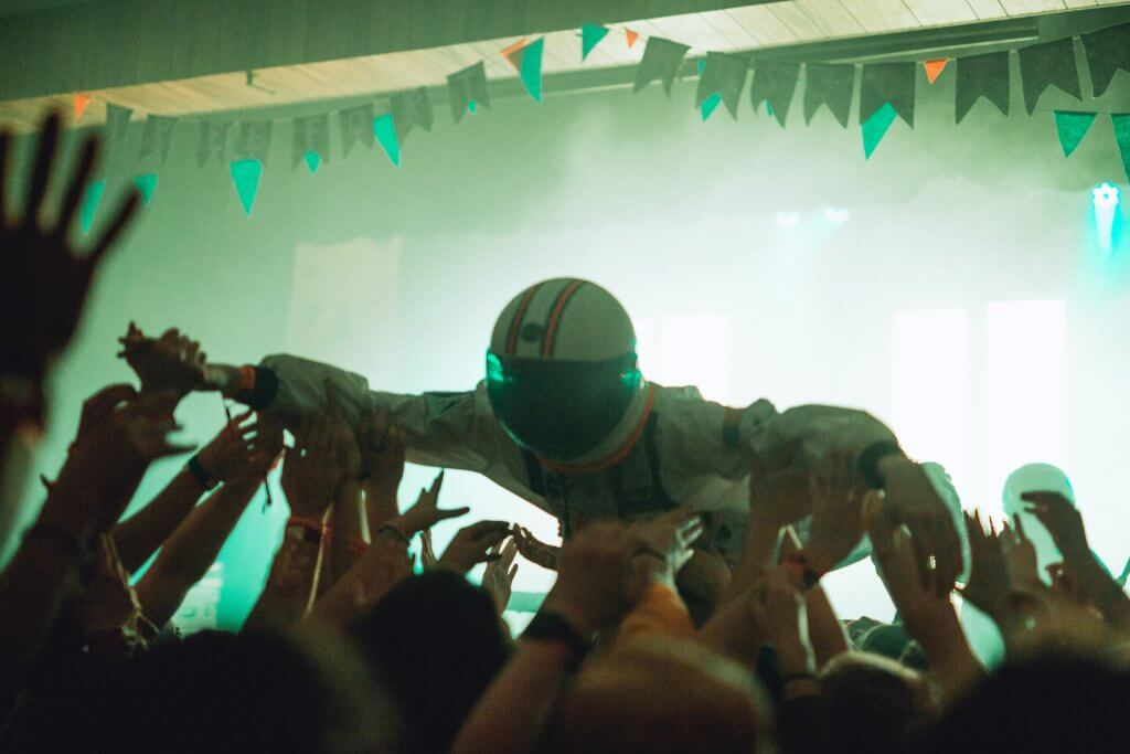 person dressed as astronaut crowd surfing