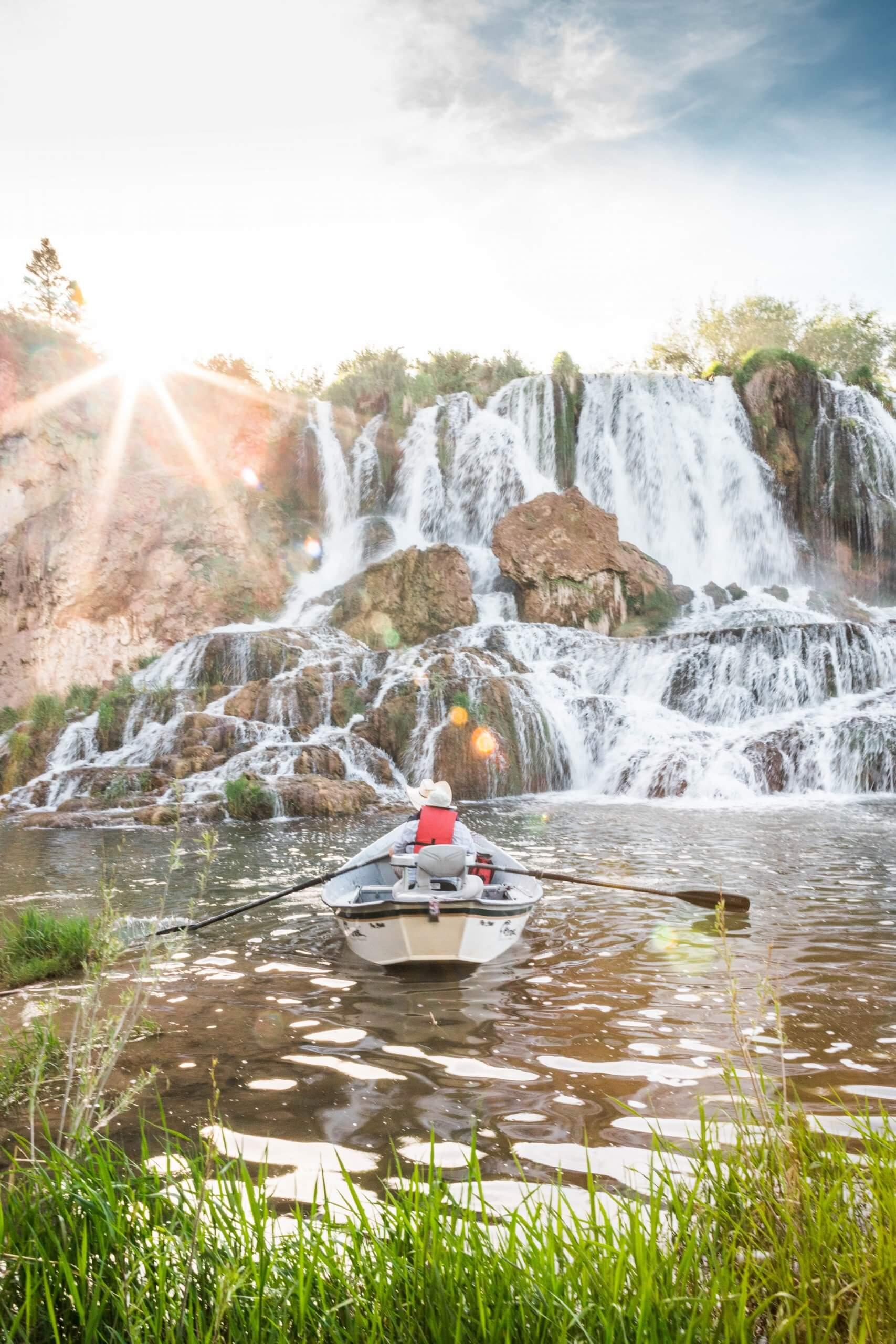 drift boat in front of waterfall