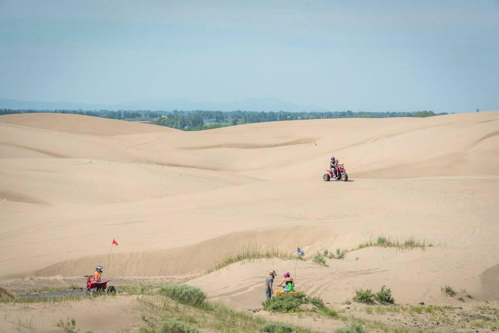 people on atvs riding on sand dunes