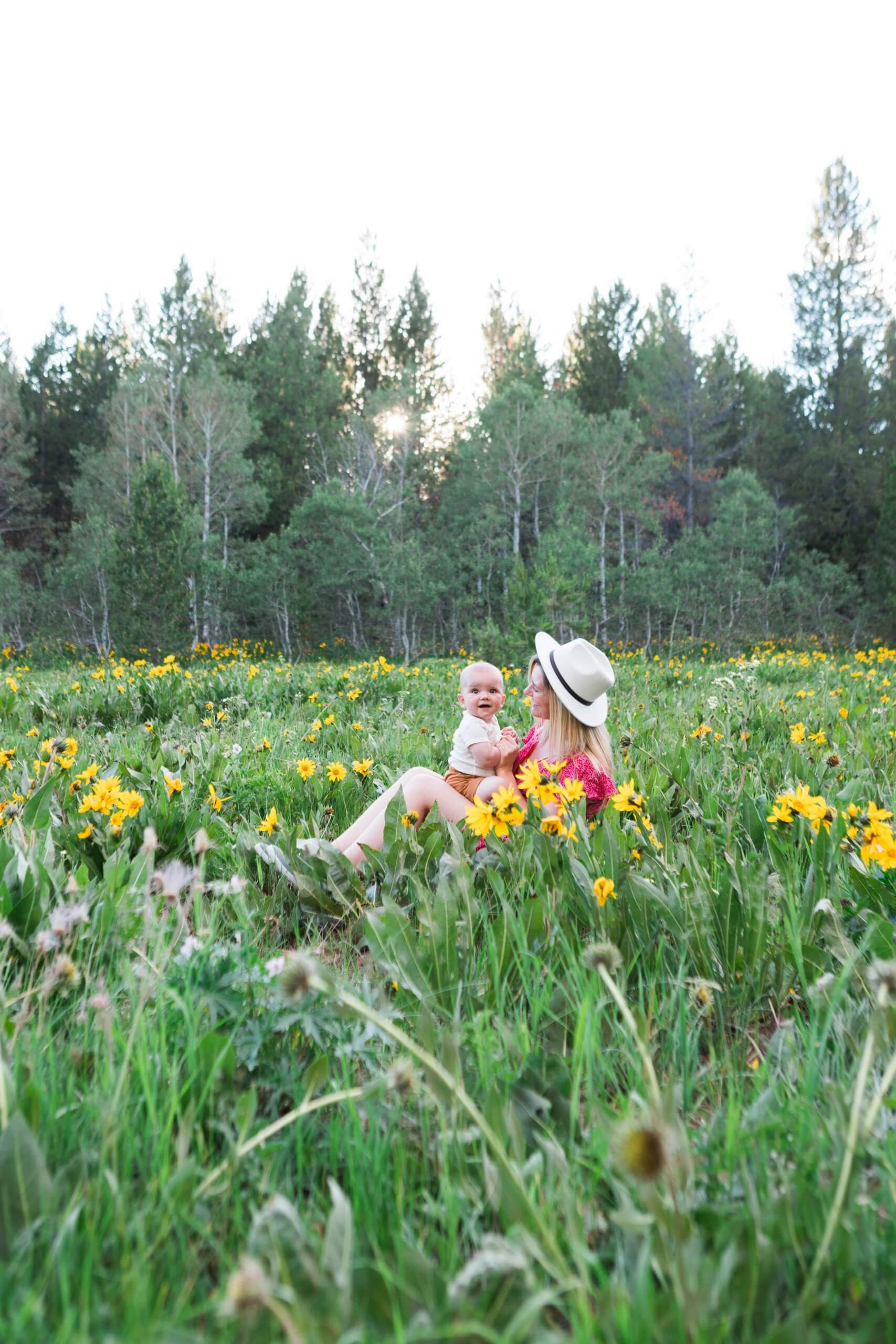 woman and baby sitting in field of wildflowers