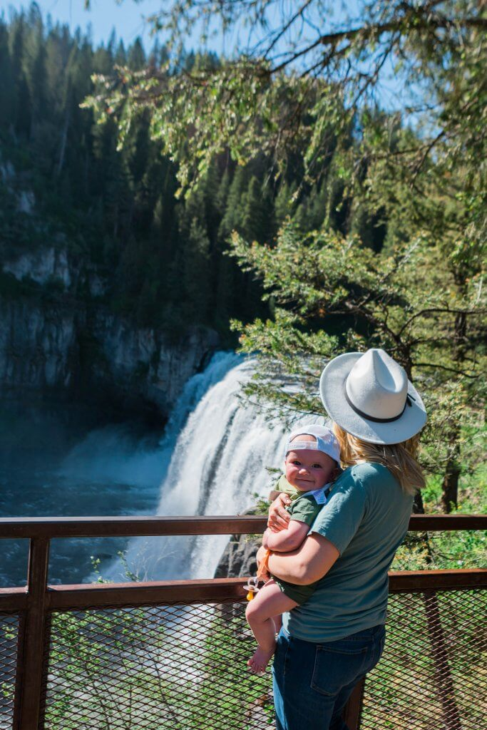 woman and baby looking at waterfall