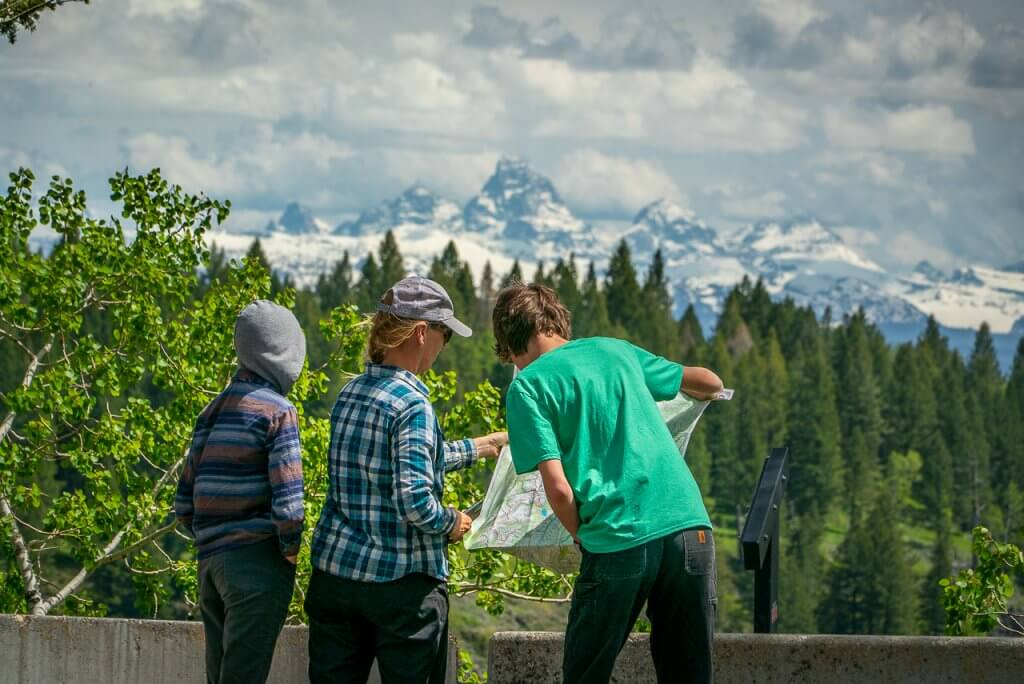 three people reading interpretive sign with teton mountains in background