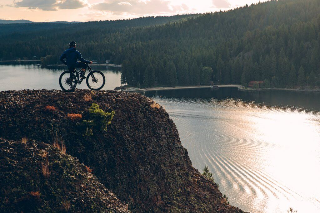 a person on a mountain bike on a hill overlooking a lake with tree covered mountains in the distance