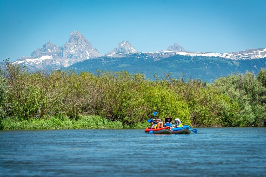 two people in inflatable kayaks with Teton mountains in background